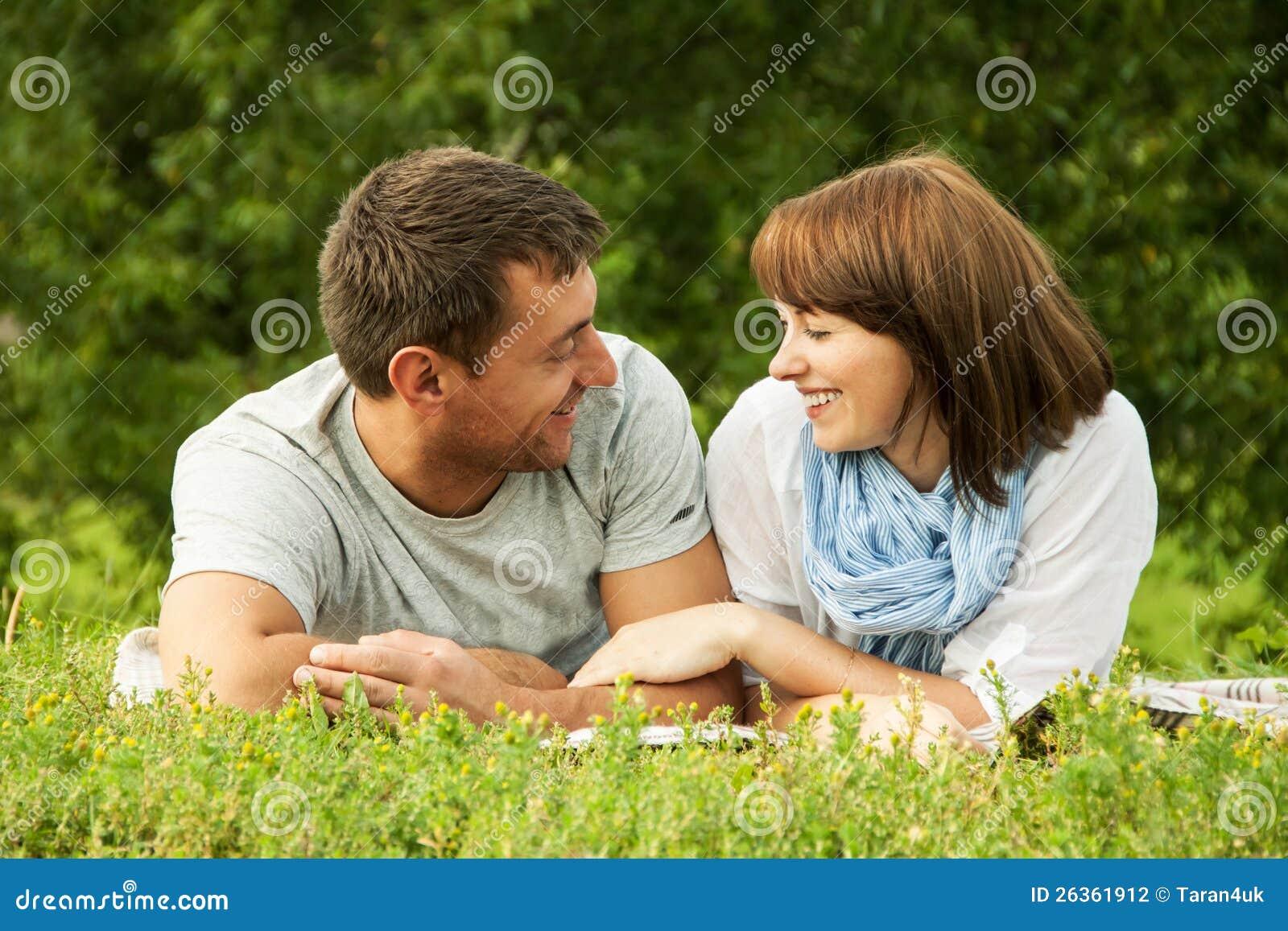 Lächelnde Paare und Lügen auf dem Gras outdoo