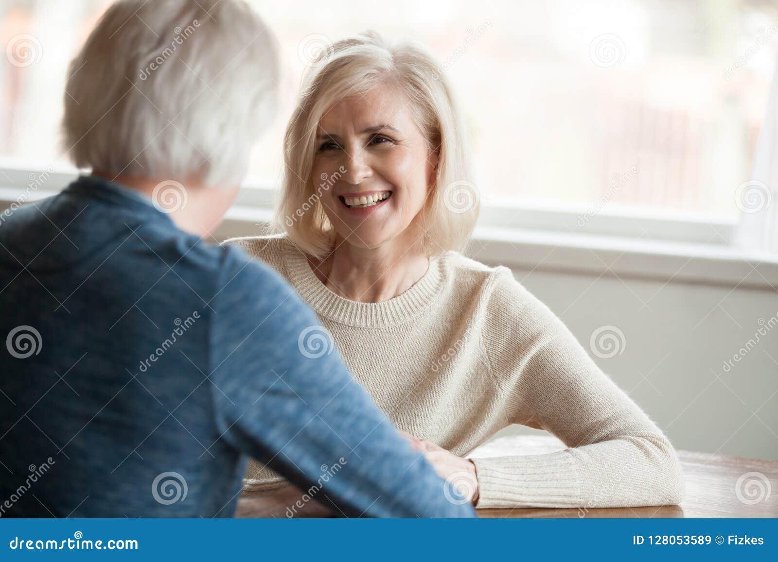 Lächelnde reife Frau, die auf den sprechenden Mann, alte Paardatierung hört