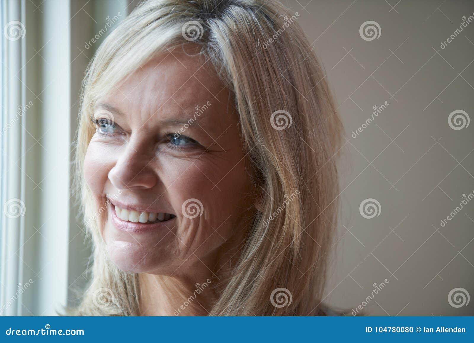 Lächelnde reife Frau, die nahe bei Fenster steht
