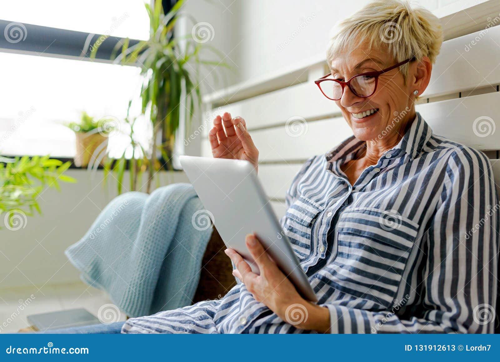 Lächelnde schöne ältere Frau, die zu Hause digitale Tablette verwendet