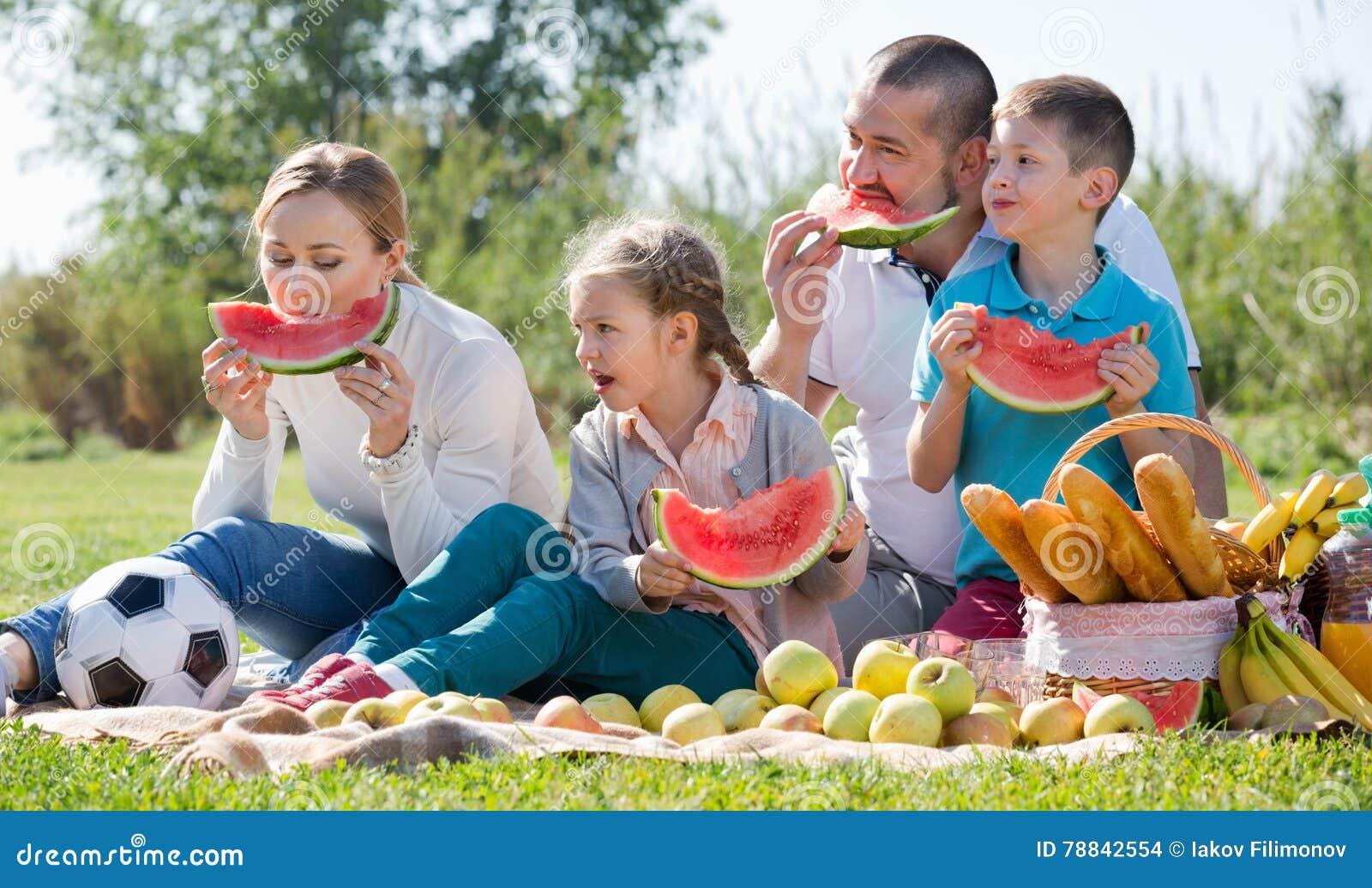 Lächelnde vierköpfige Familie, die Picknick und das Essen der Wassermelone hat