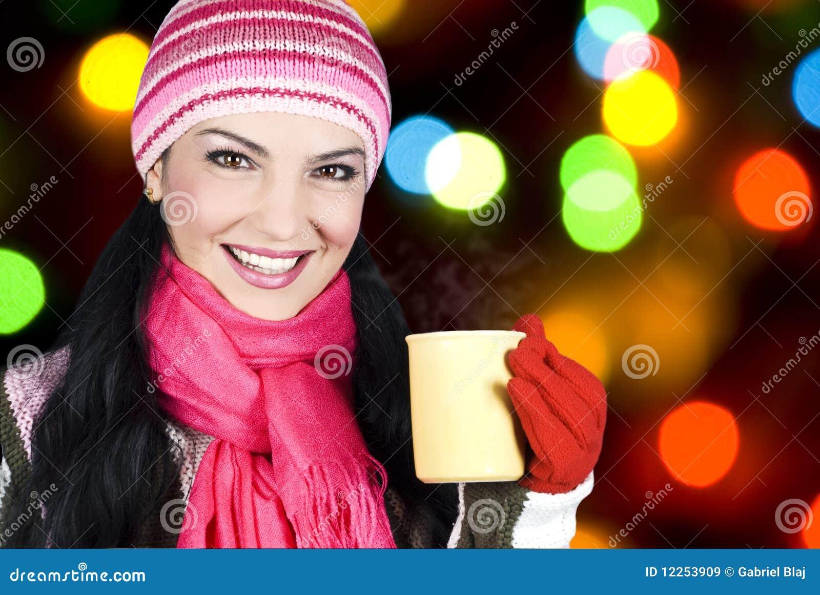 Lächelnde Winterfrau, die heißen Tee anhält