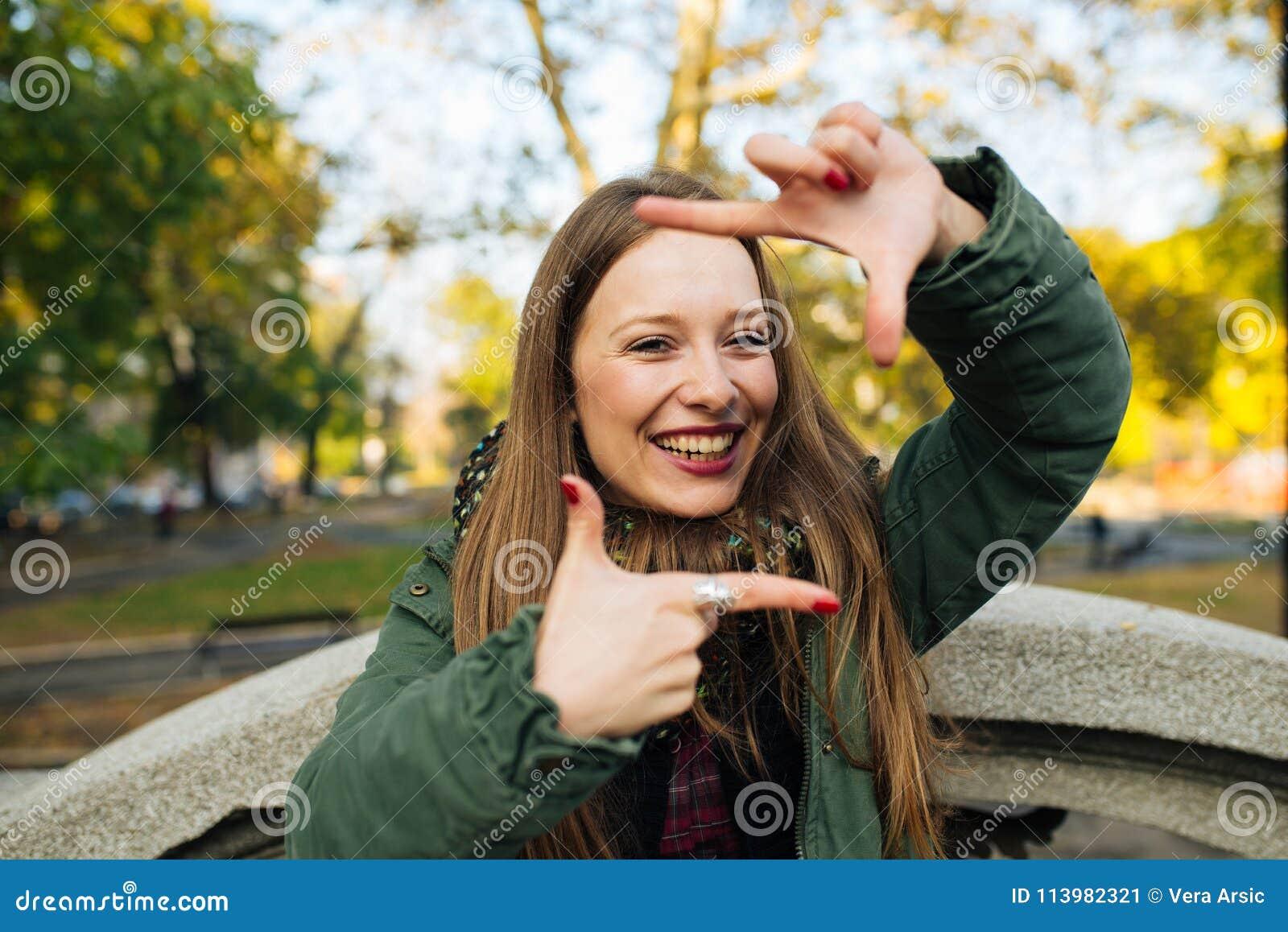 Lächelnder asiatischer Geschäftsmann, der einen Rahmen mit den Fingern, lokalisiert auf weißem Hintergrund macht