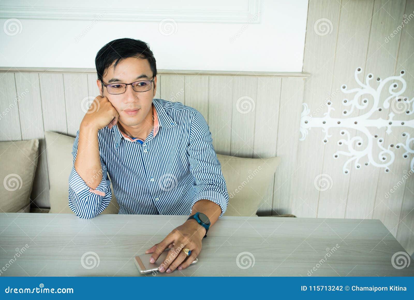 Lächelnder asiatischer Mann im zufälligen gekleideten Ausarbeiten des Büros während