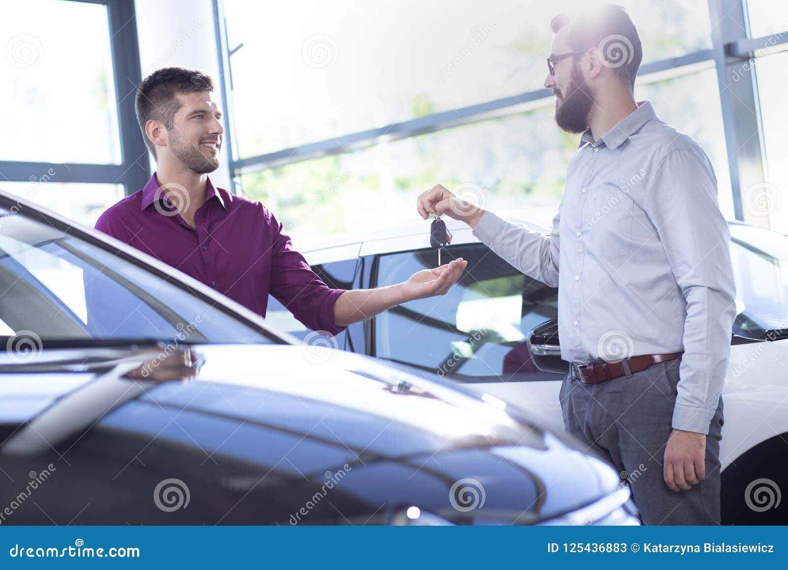 Lächelnder Autohändler, der dem neuen Käufer in einem behandelnden Salon Schlüssel gibt