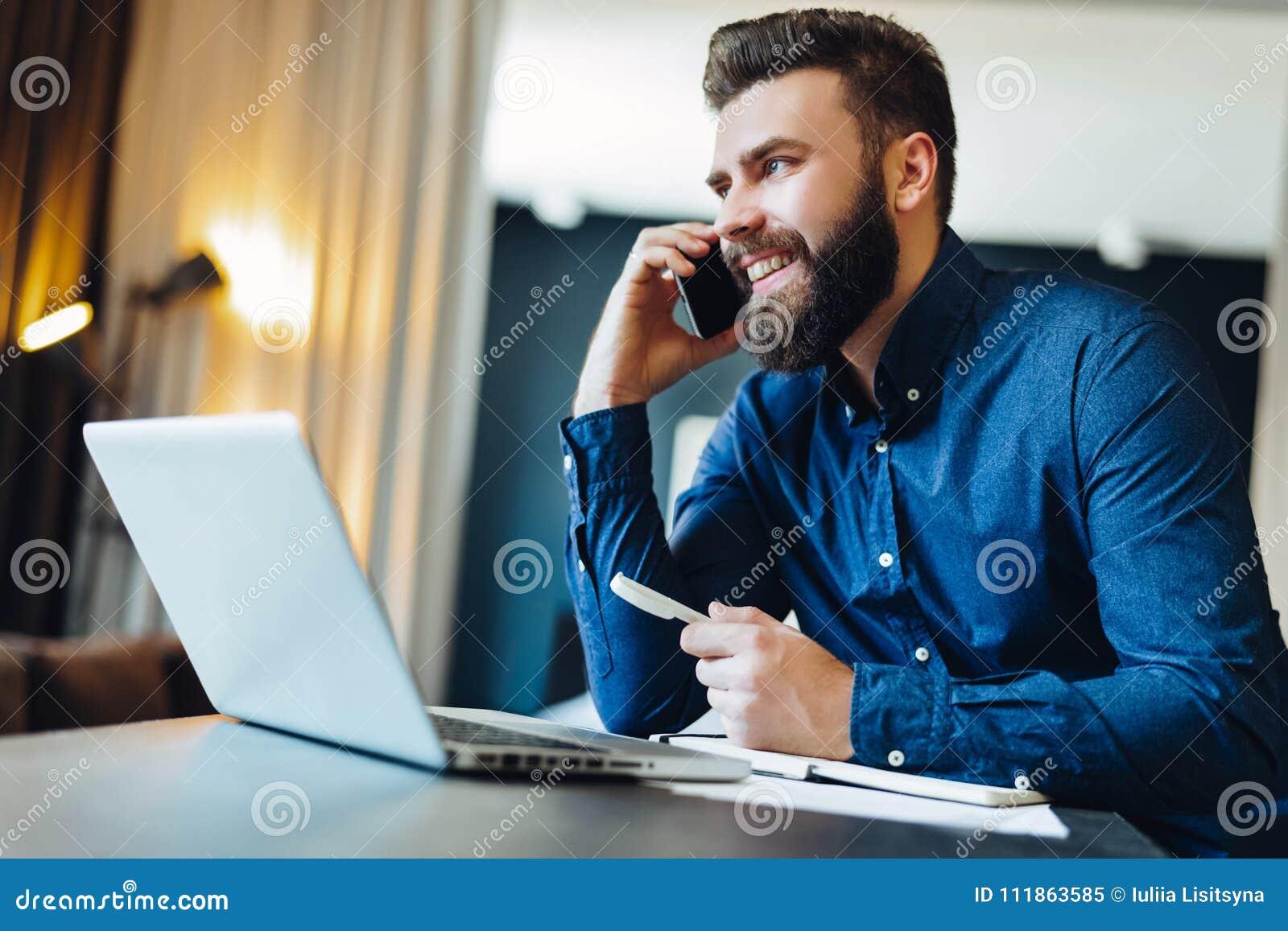 Lächelnder bärtiger Geschäftsmann der Junge, der vor dem Computer, sprechend am Handy, Behälter sitzt Telefongespräche