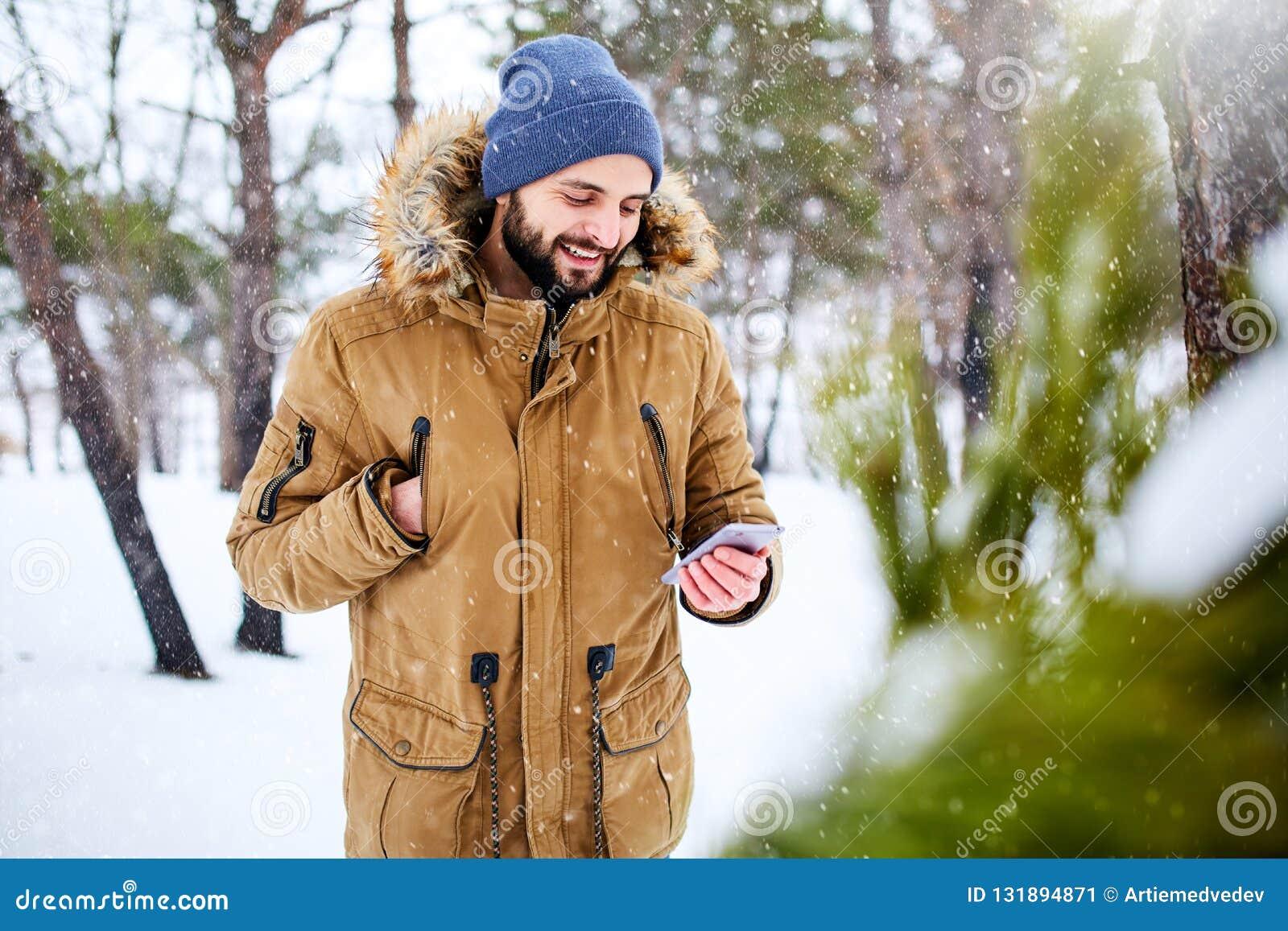 Lächelnder bärtiger Mann trägt warme Winterkleidung und -anwendung von Smartphone mit schnellem Internetanschluss in der Landseit