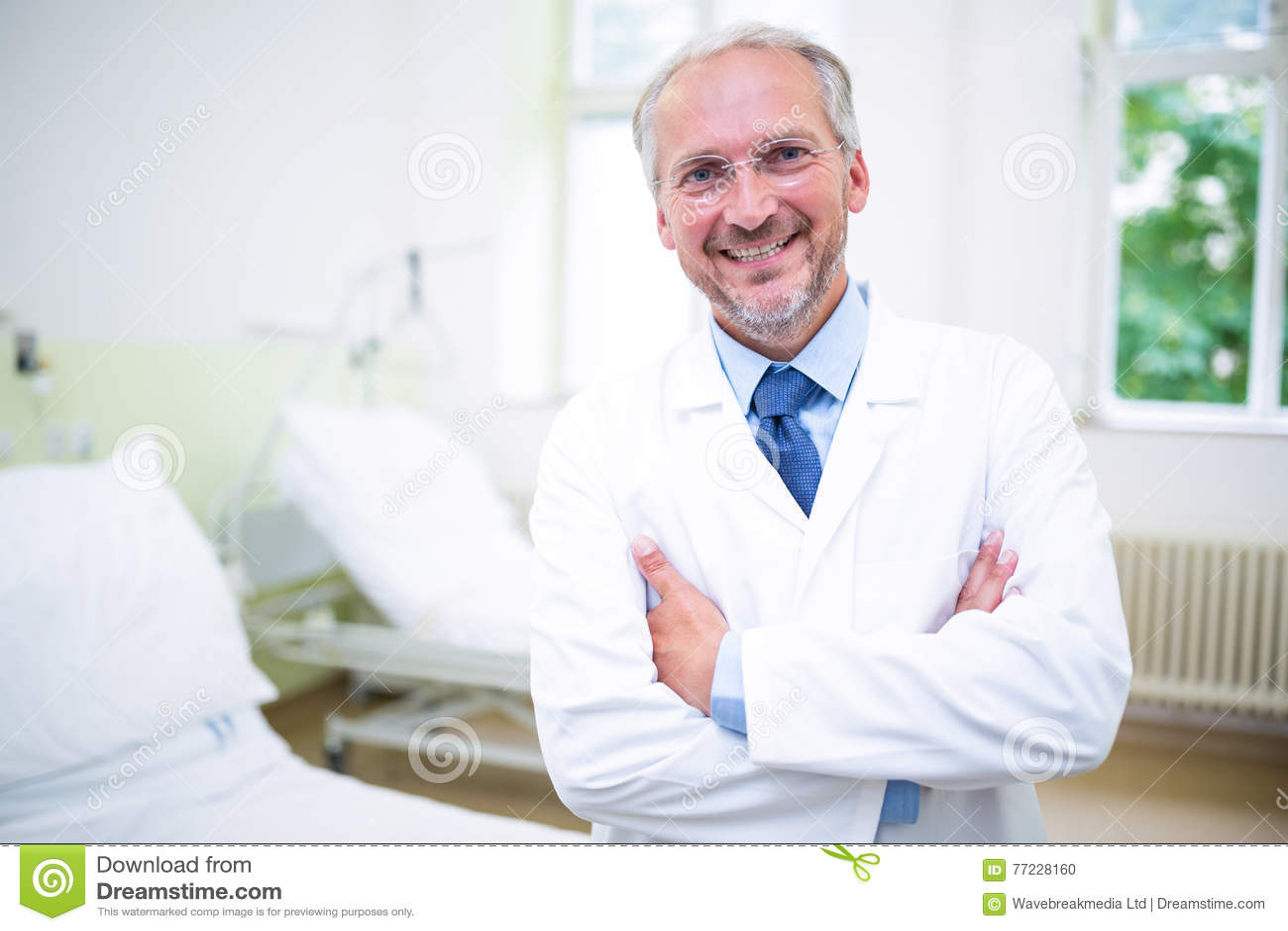 Lächelnder Doktor, der mit den Armen gekreuzt steht