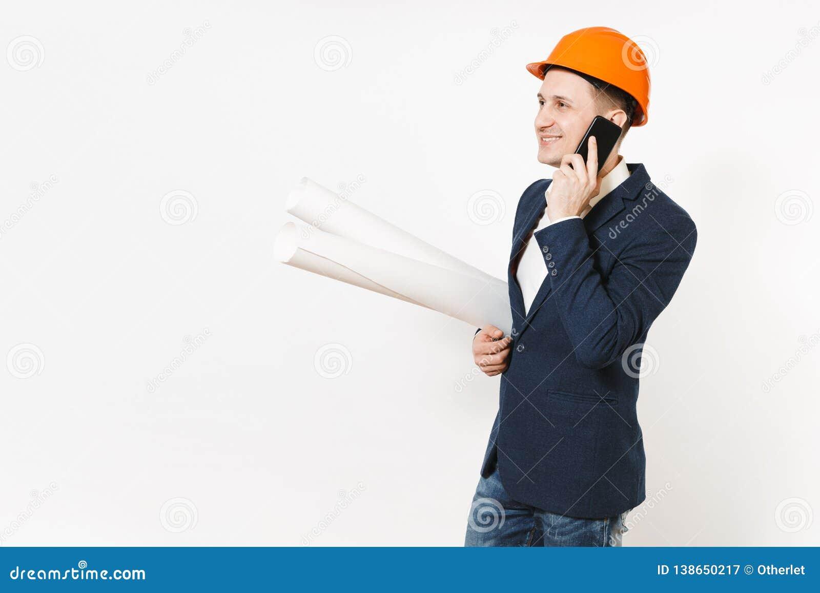 Lächelnder Geschäftsmann im dunklen Anzug, schützender Hardhat, der Planpläne hält, am Handy spricht und beiseite schaut
