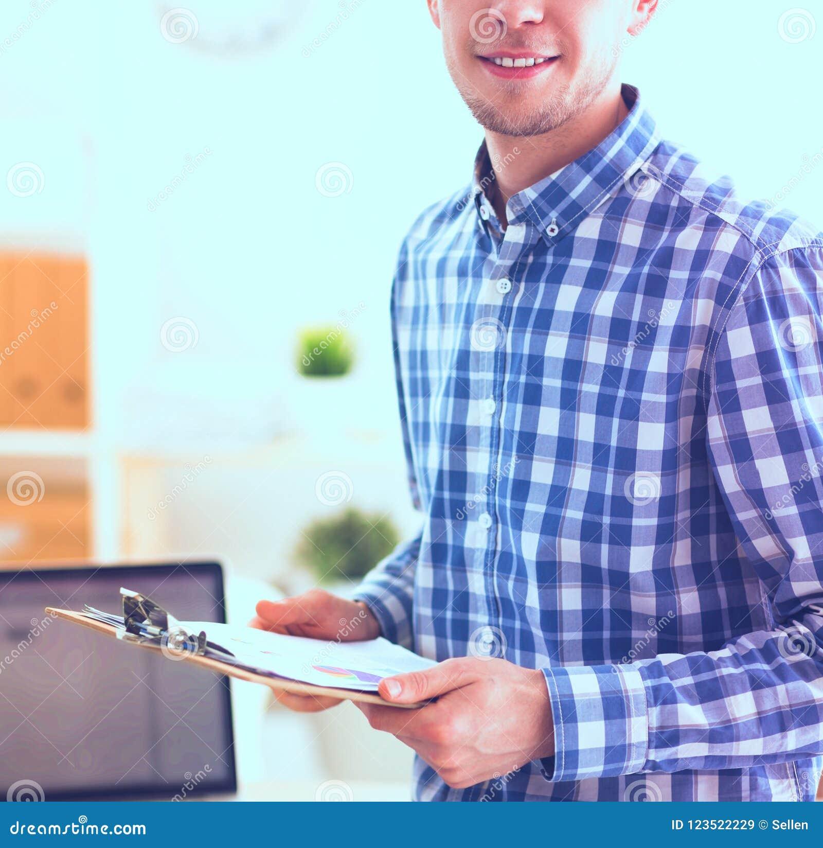 Lächelnder Geschäftsmann mit dem roten Ordner, der im Büro sitzt