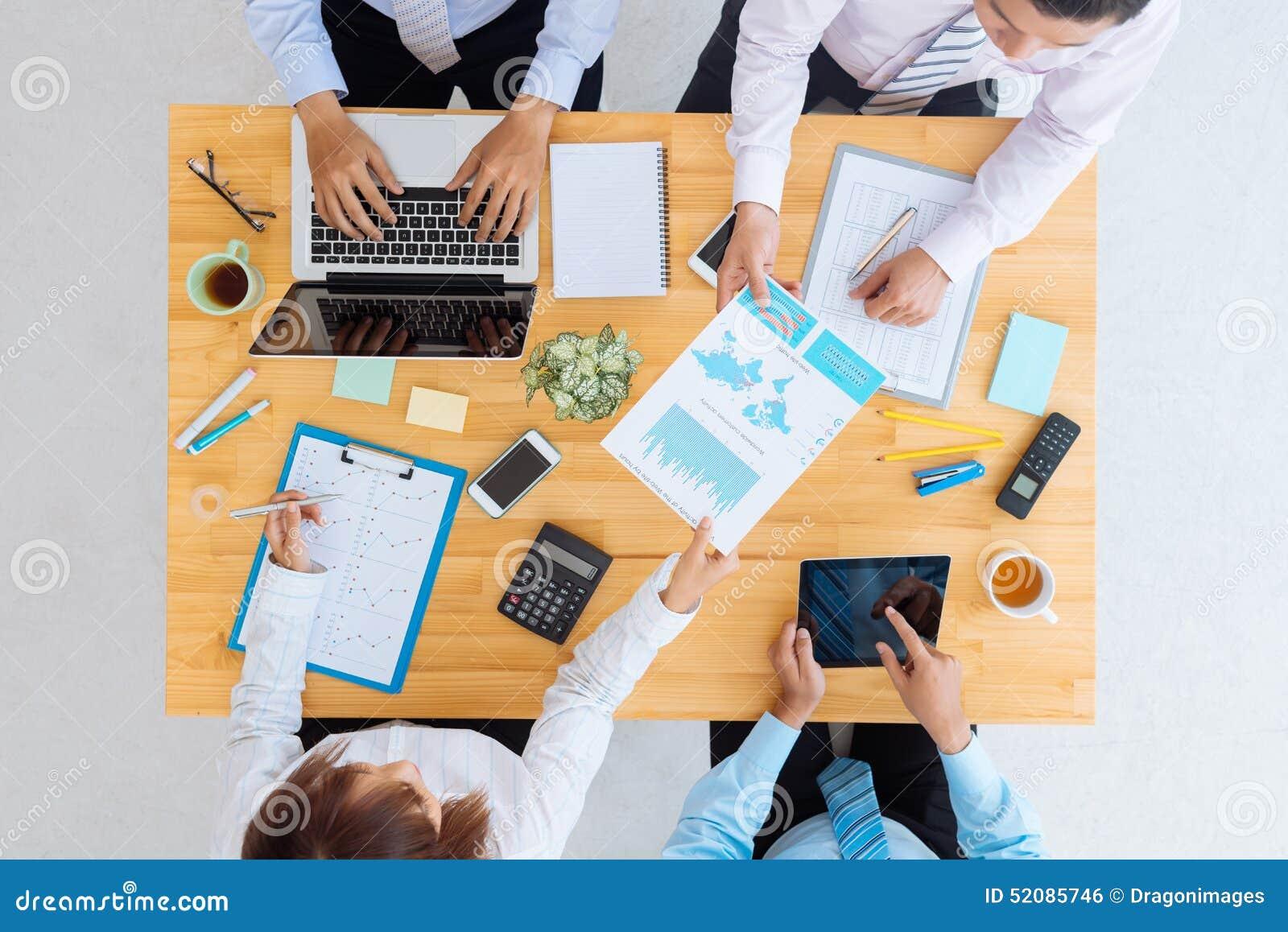 Lächelnder Geschäftsmann unter Verwendung des Laptop cmputer am Schreibtisch und Unterhaltung mit einer Frau