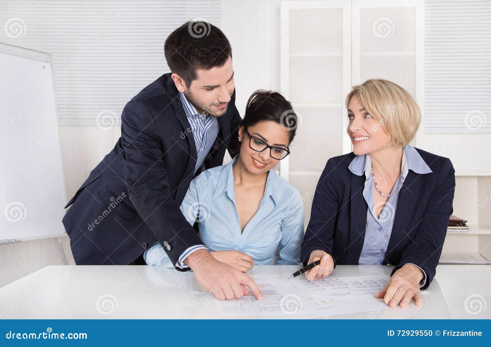 Lächelnder Geschäftsmann unter Verwendung des Laptop cmputer am Schreibtisch und Unterhaltung mit einer Frau Drei Leute, die am T