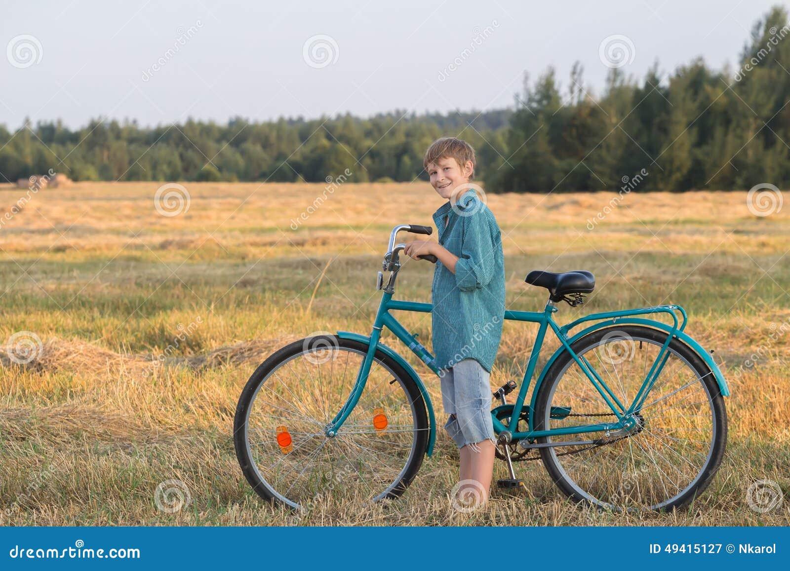 Download Lächelnder Jugendlichjunge, Der Fahrrad Auf Dem Bauernhofgebiet Hält Stockbild - Bild von zicklein, field: 49415127