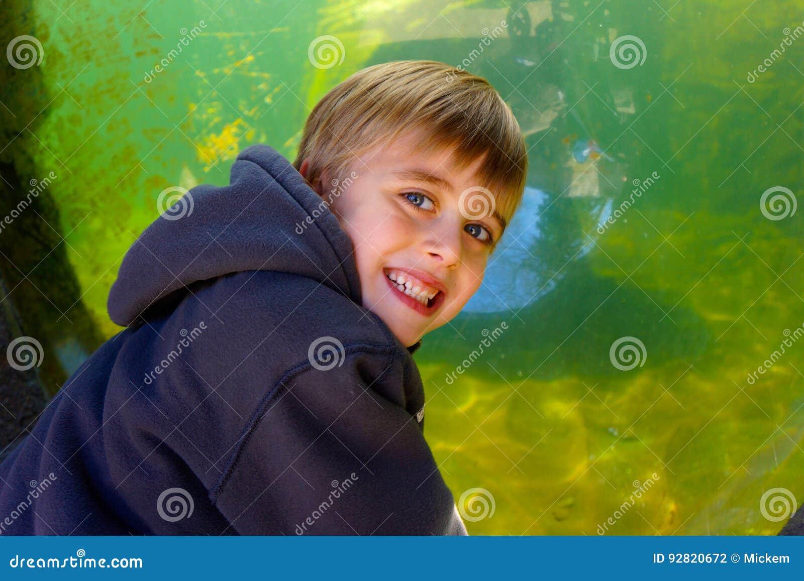 Lächelnder Junge mit Aquariumbehälter im Hintergrund