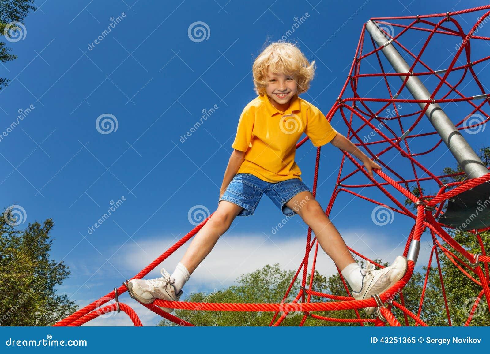 Lächelnder Junge steht auf rotem Seil mit den Beinen auseinander