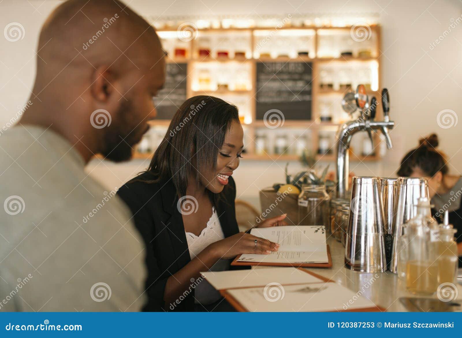 Lächelnder junger Afroamerikaner verbinden Lesemenüs in einer Stange