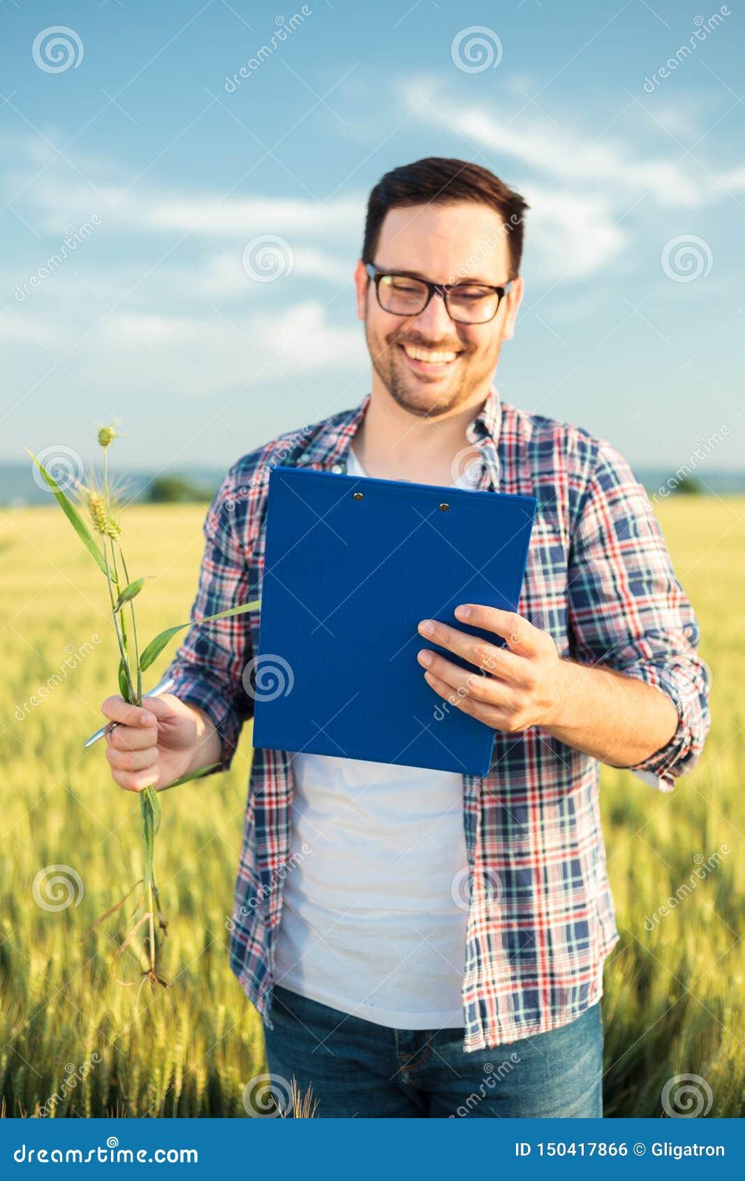 Lächelnder junger Agronom oder Landwirt, die Weizenfeld vor der Ernte, Daten zu einem Klemmbrett schreibend kontrolliert Selektiv