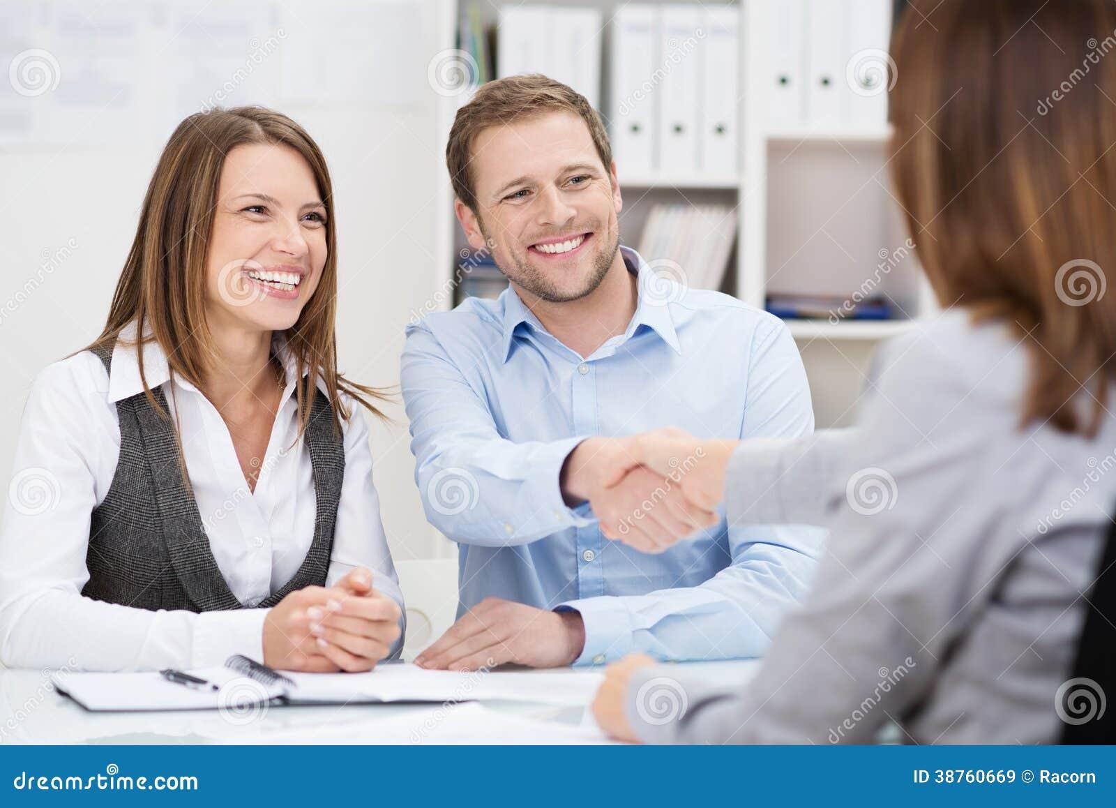 Lächelnder junger Mann, der Hände mit einem Mittel rüttelt