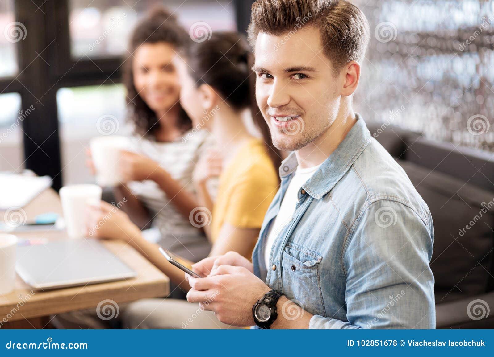 Lächelnder junger Mann, der sein Telefon verwendet
