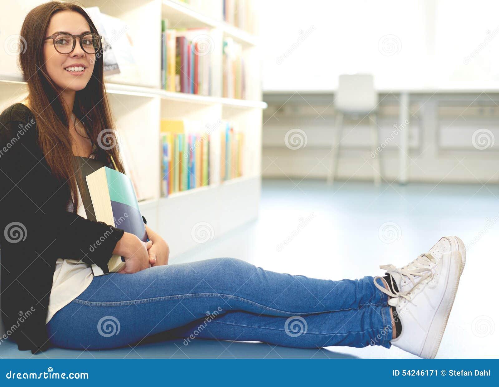 Lächelnder junger Student, der sich auf dem Campus entspannt