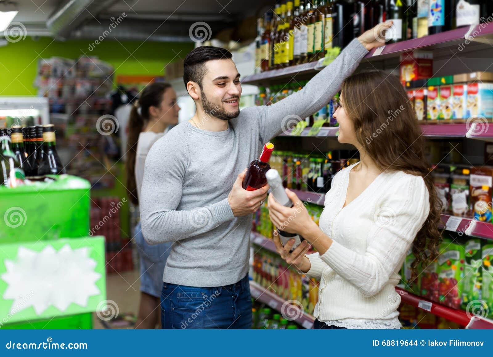 Lächelnder kaufender Wein der Paare