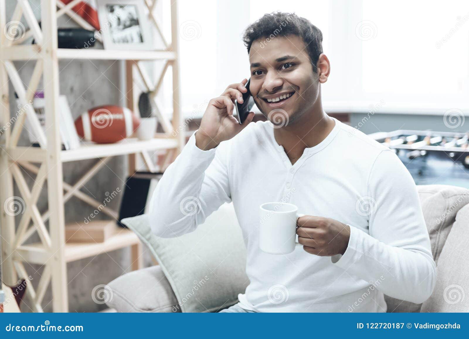 Lächelnder Kerl in der Freizeitbekleidung unter Verwendung des Handys