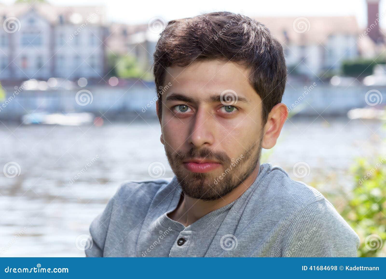 Lächelnder Mann mit Bart in einem grauen Hemd auf einem Fluss
