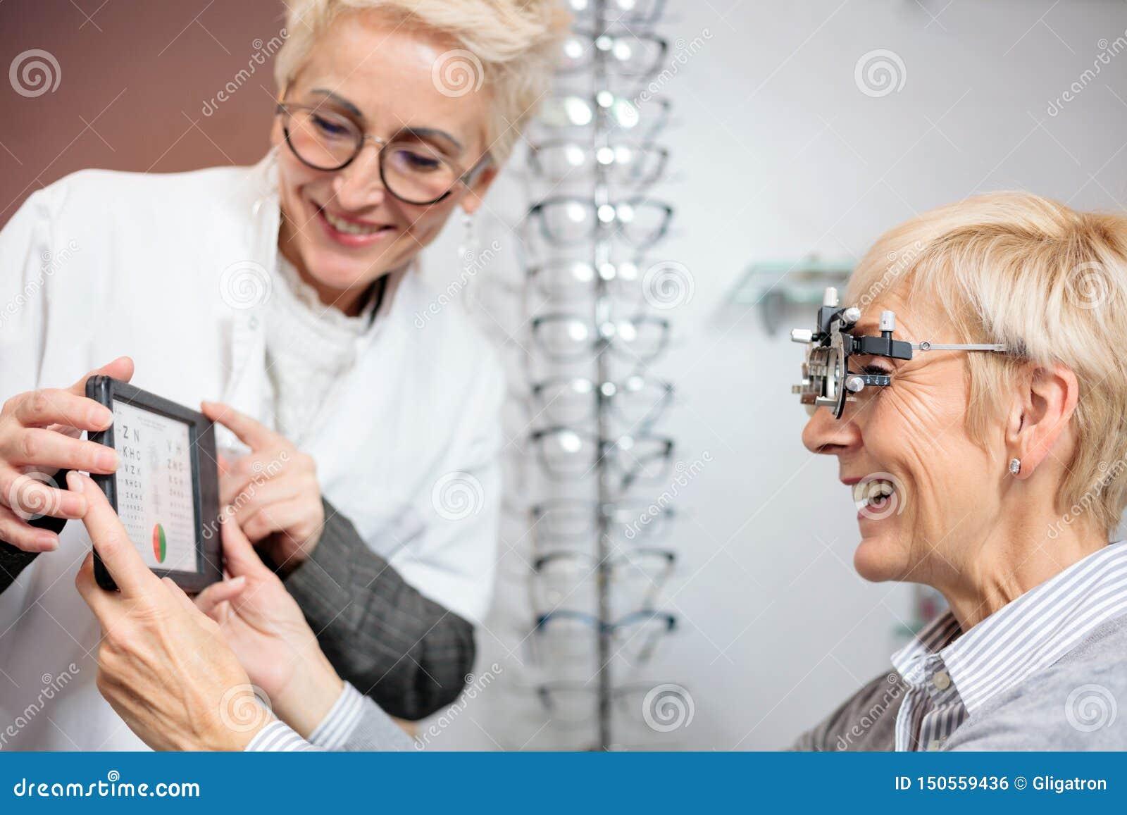 Lächelnder reifer weiblicher Augenarzt, der die ältere Frau, eine Sehtafel halten überprüft