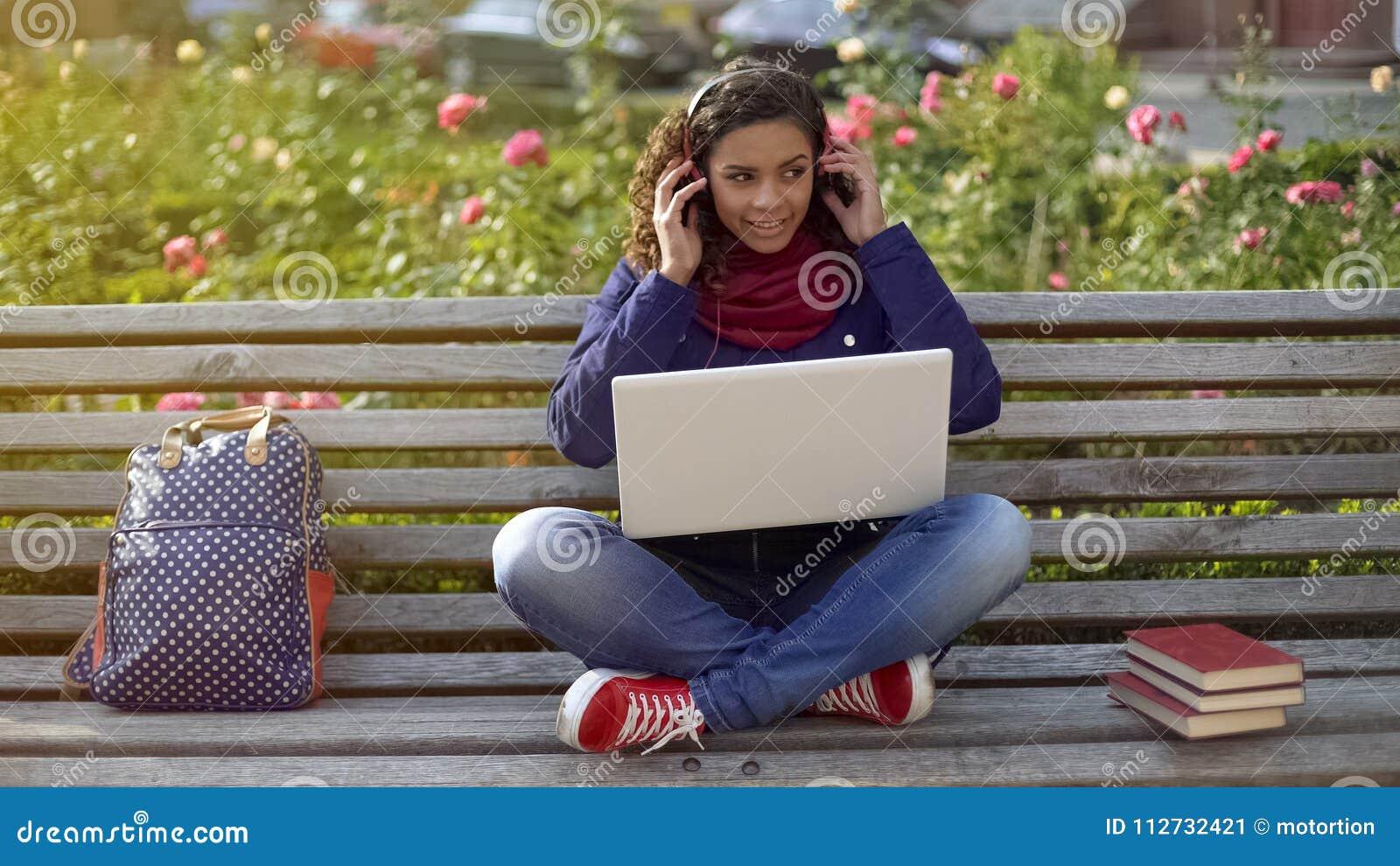 Lächelnder Student in den Kopfhörern, die auf der Bank, hörend auf Lieblingstitelliste sitzen