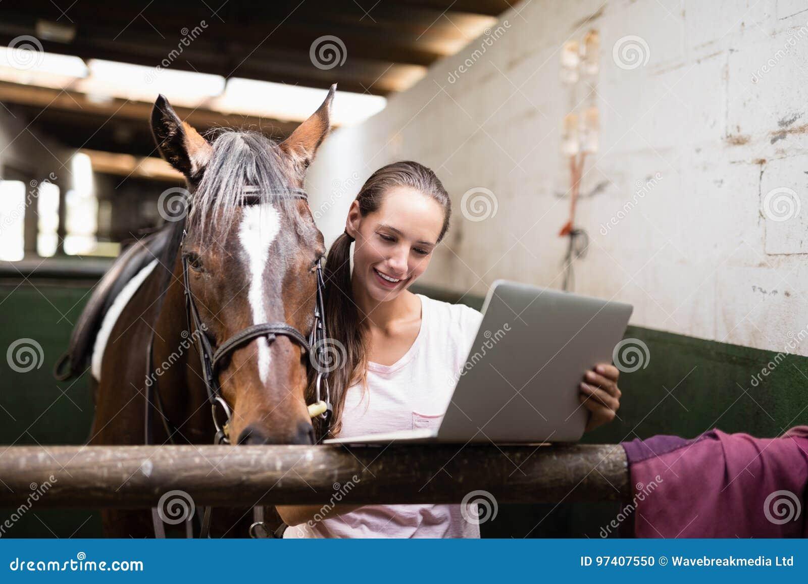 Lächelnder weiblicher Jockey, der Laptop beim Bereitstehen des Pferds verwendet