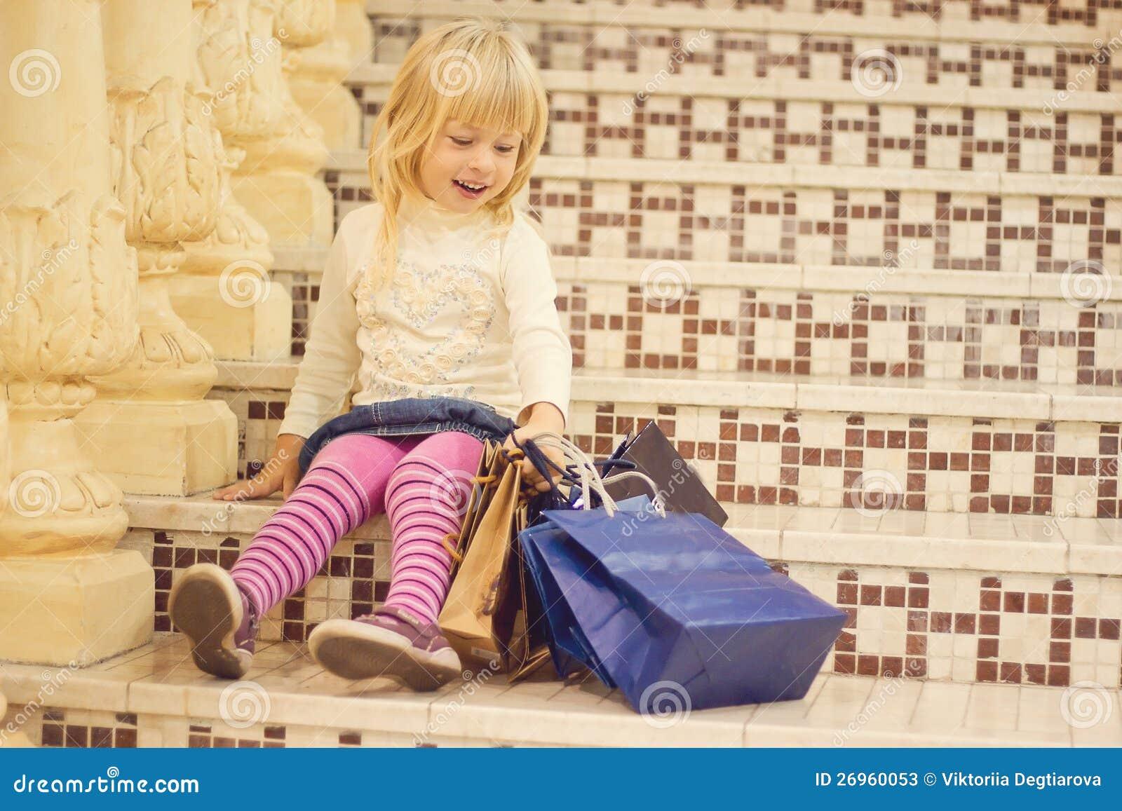 lächelndes blondes mädchen 3 jahre alt mit dem einkaufen