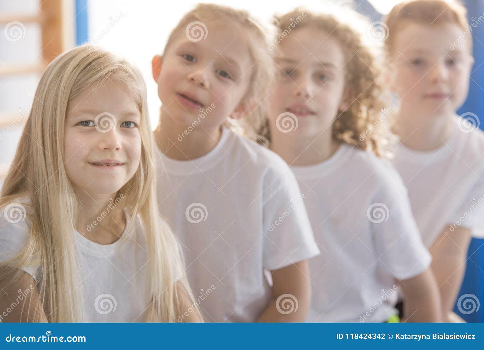 Lächelndes blondes Mädchen mit Freunden
