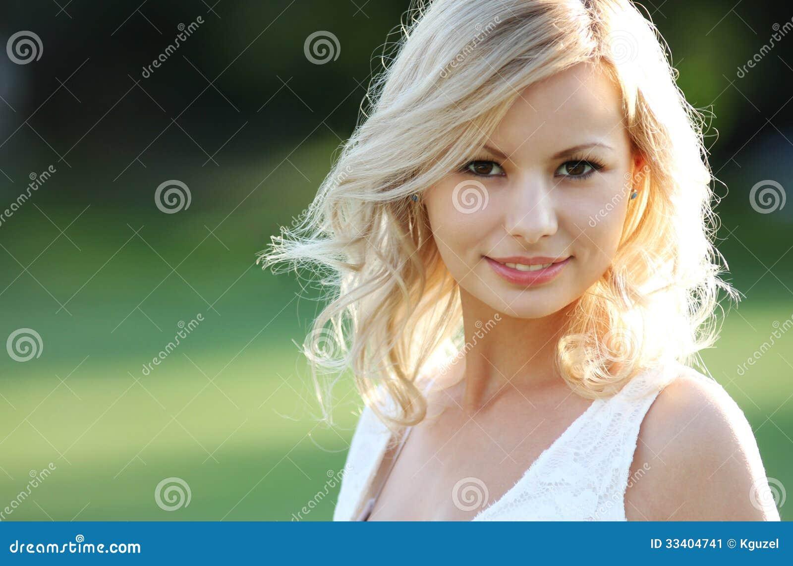 Lächelndes blondes Mädchen. Porträt der glücklichen netten schönen jungen Frau, draußen.