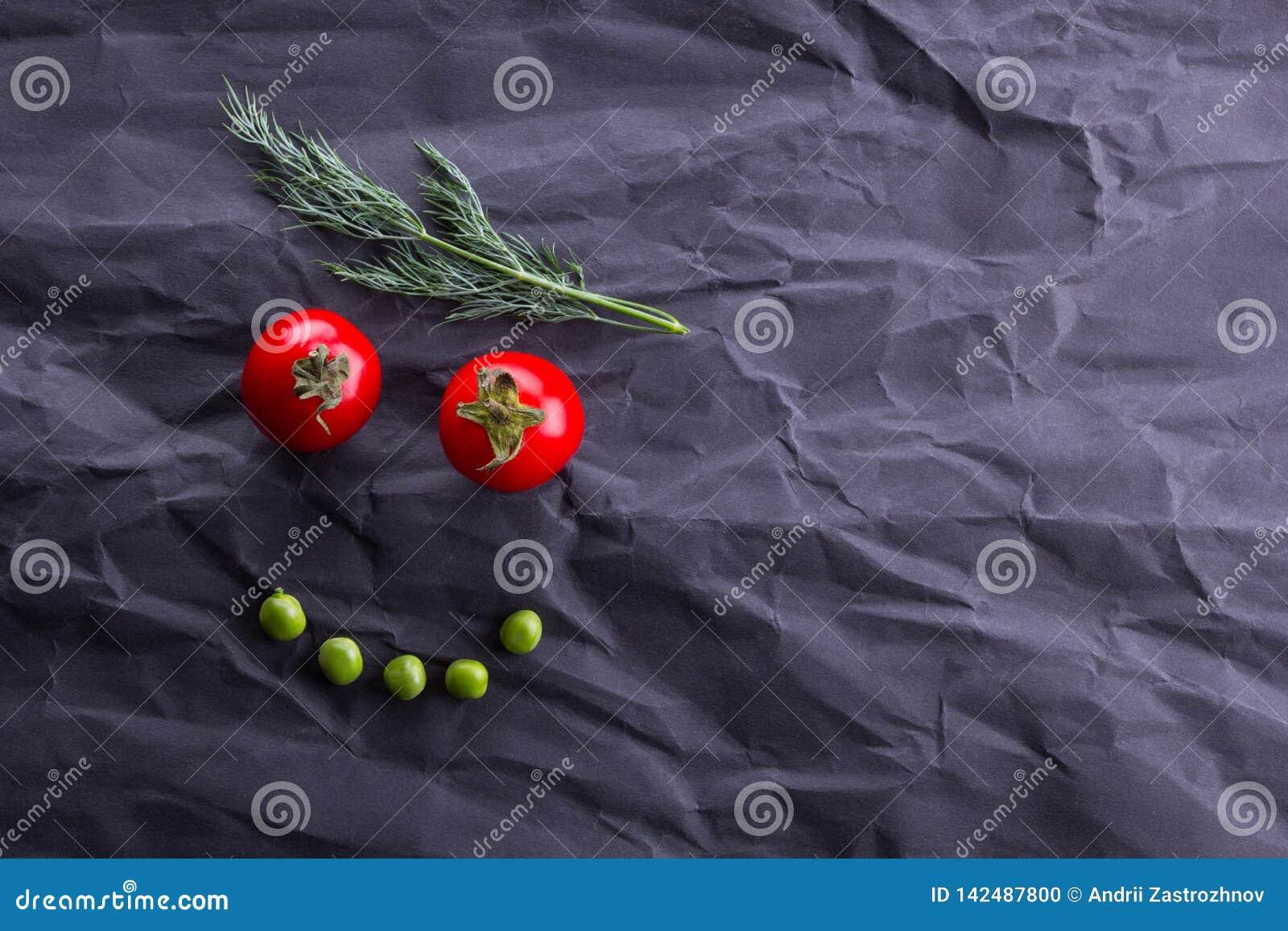 Lächelndes Gesicht vom Gemüse auf schwarzem Papierhintergrund