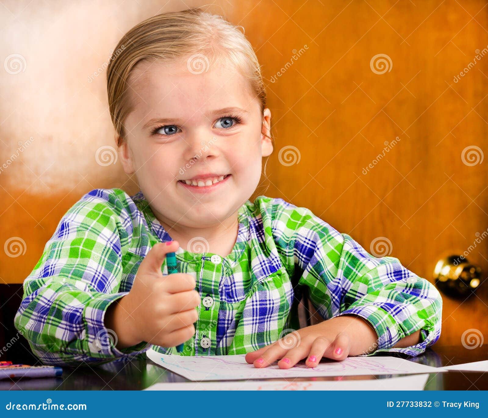 Lächelndes junges Mädchen, das eine Zeichnung tut.