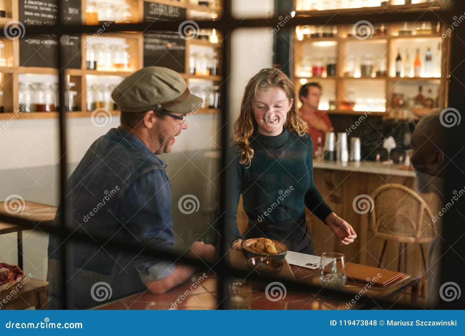 Lächelndes Kellnerinumhüllungslebensmittel zu einem Bistrokunden