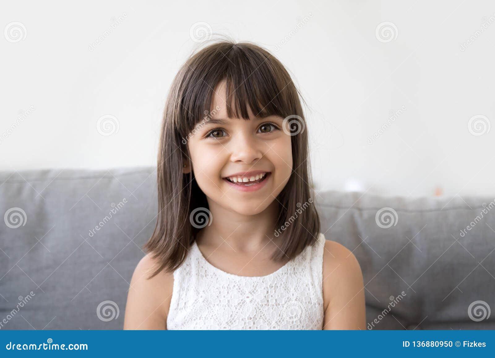 Lächelndes Kindermädchen, das mit der Kamera macht Videoanruf vlog spricht