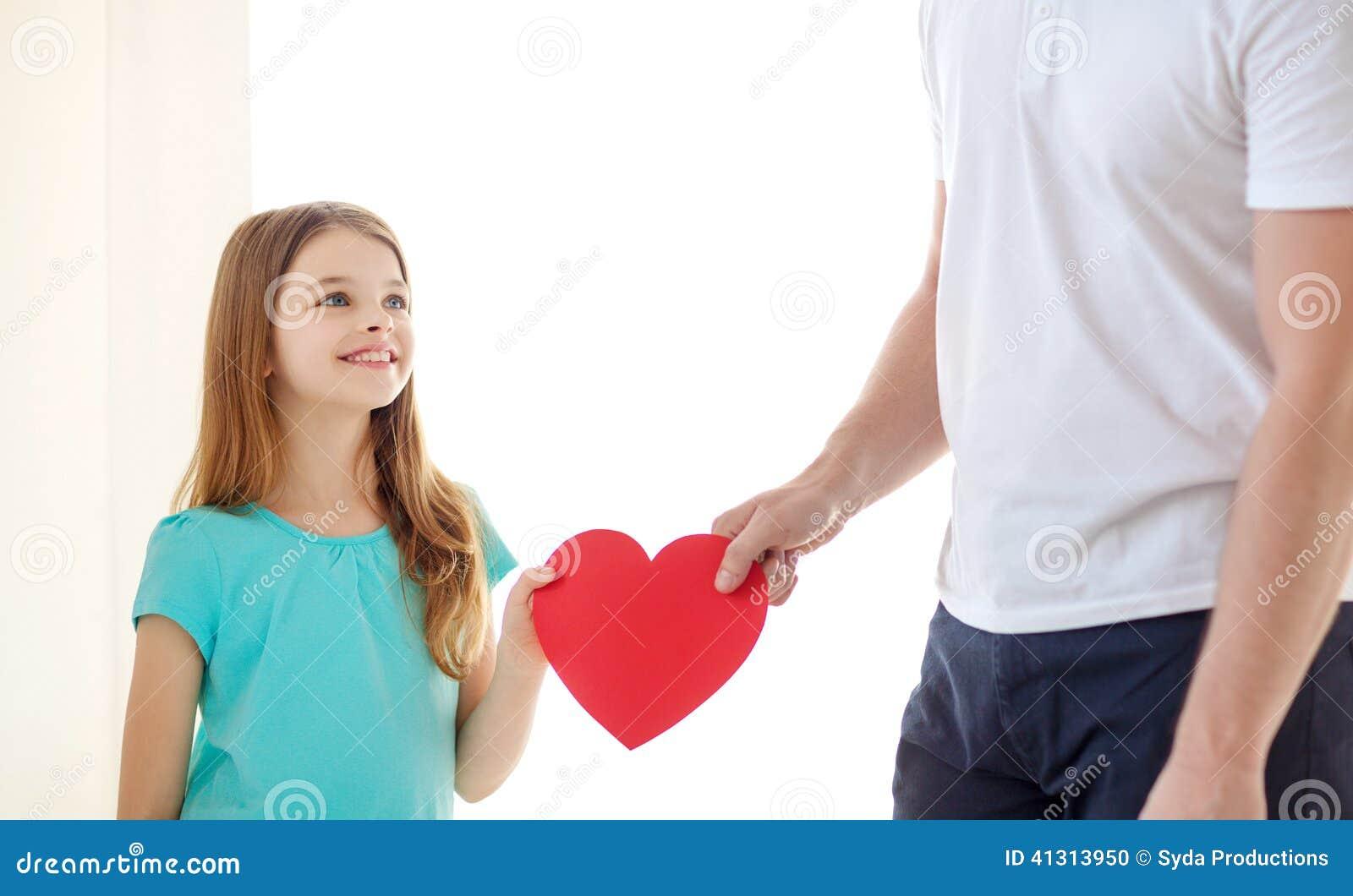 Lächelndes kleines Mädchen und Vater, die rotes Herz halten