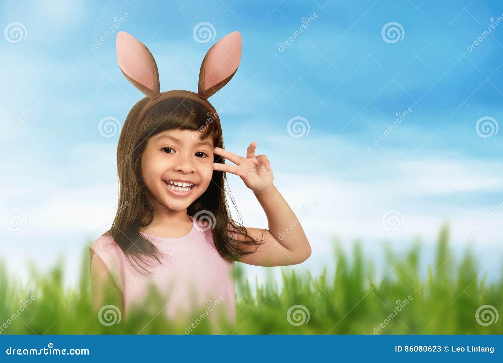 Lächelndes Mädchen, das Häschenohren in ihrem Haar verwendet
