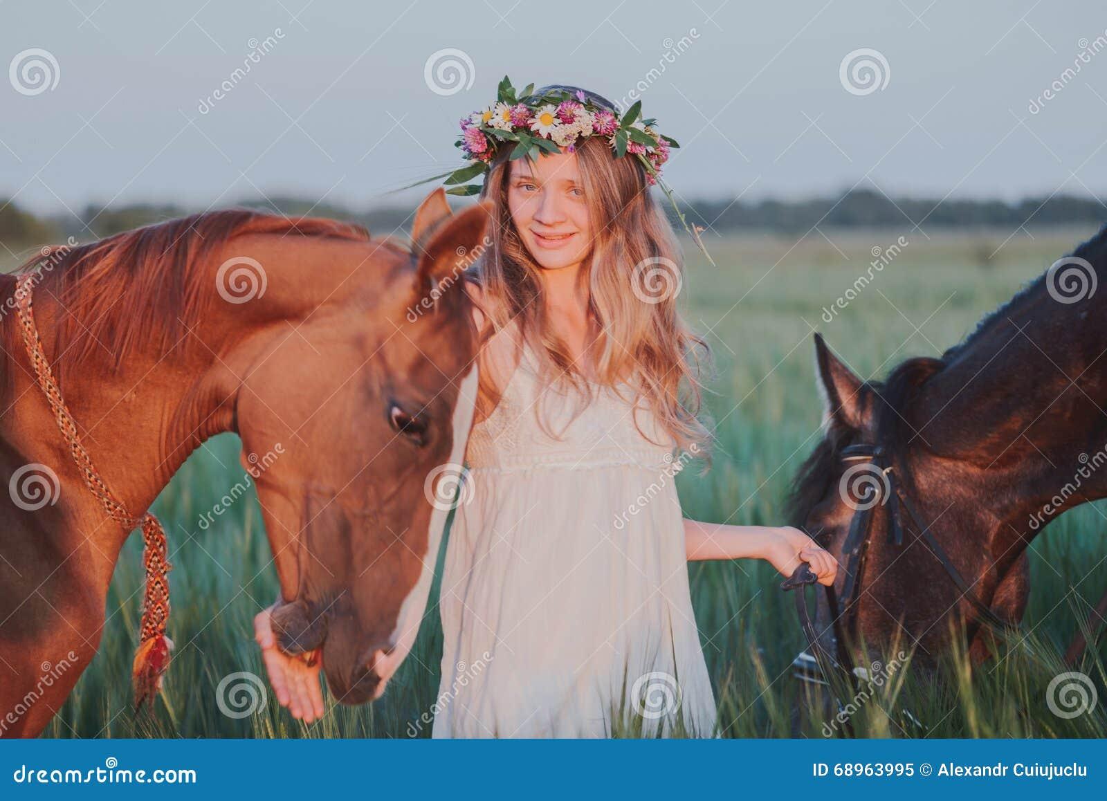 lächelndes mädchen im blumenkranz mit pferd heißer