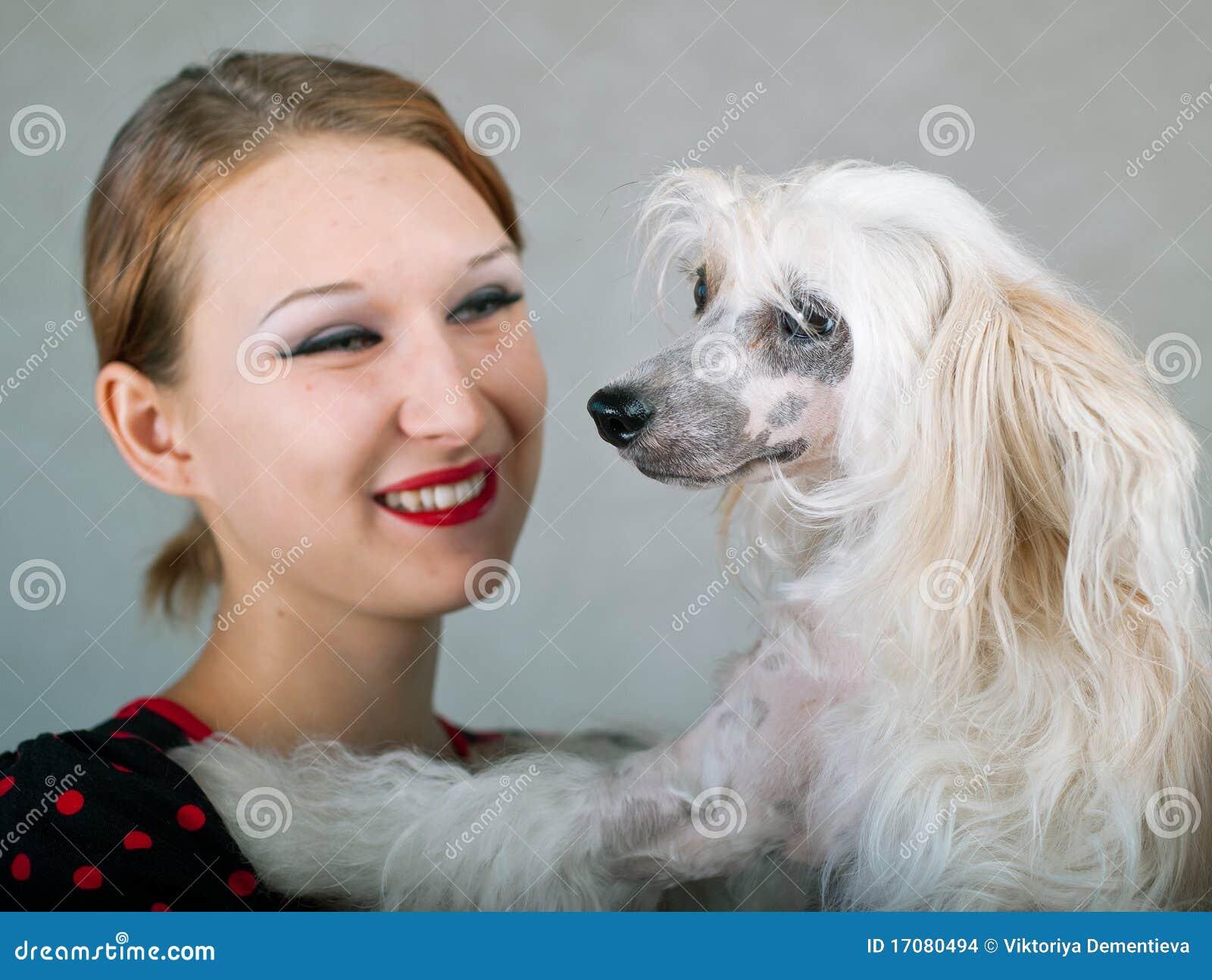 Lächelndes Mädchen und chinesischer mit Haube Hund