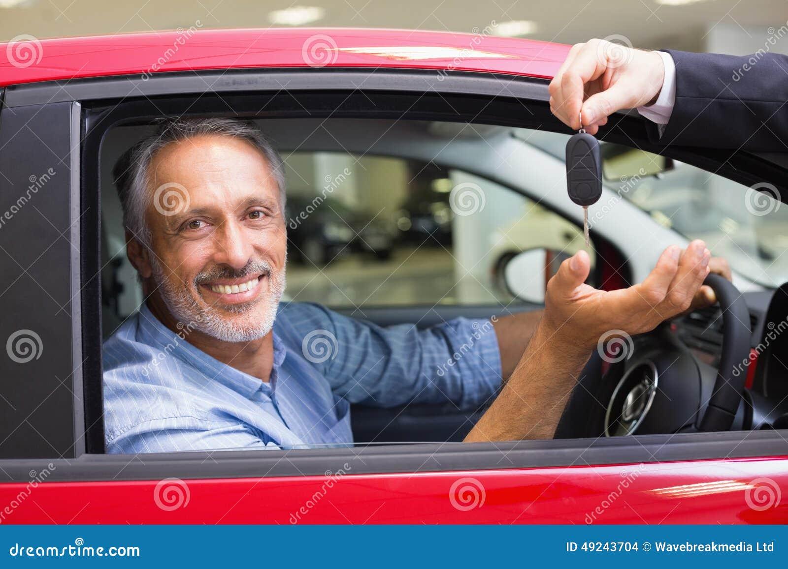 Lächelndes Mannautofahren während Verkäufer sein gebender Schlüssel