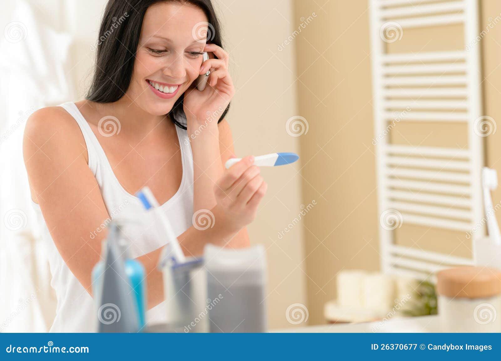 Lächelndes Schwangerschaft-Testergebnis der Frau positives