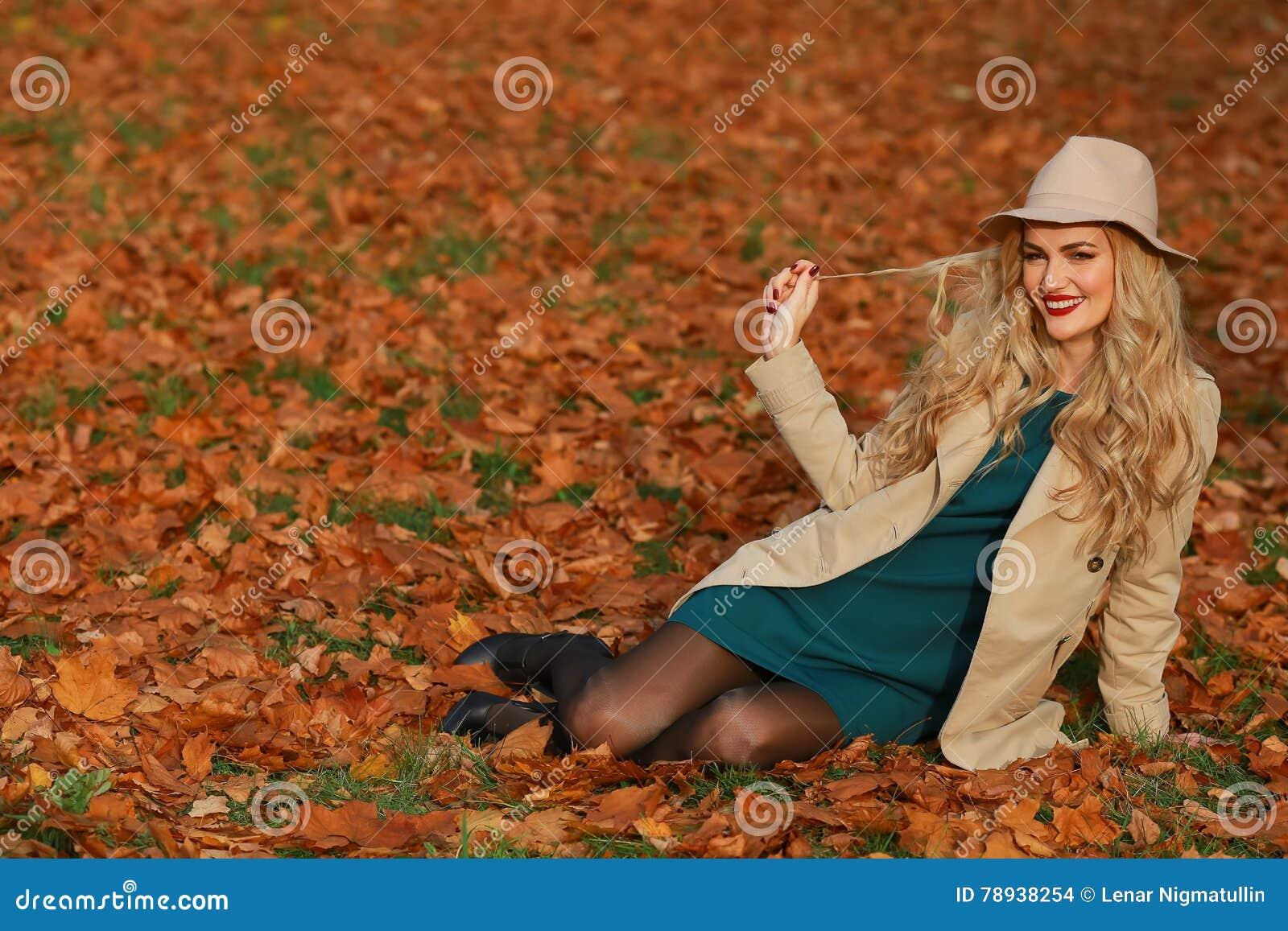 Lächelndes Sitzen der jungen Frau auf dem Gras im Herbst Ahorn-Gartenhintergrund des Falles gelber Schönes Mädchen im Mantel und