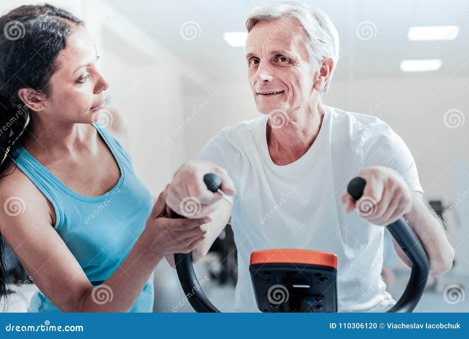 Lächelndes Training des alten Mannes und eine ernste Frau nahe ihm