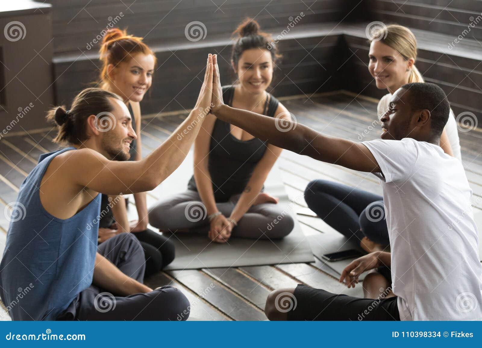 Lächelndes verschiedenes Yogateammitgliedgeben hoch--fünf an Gruppe trai