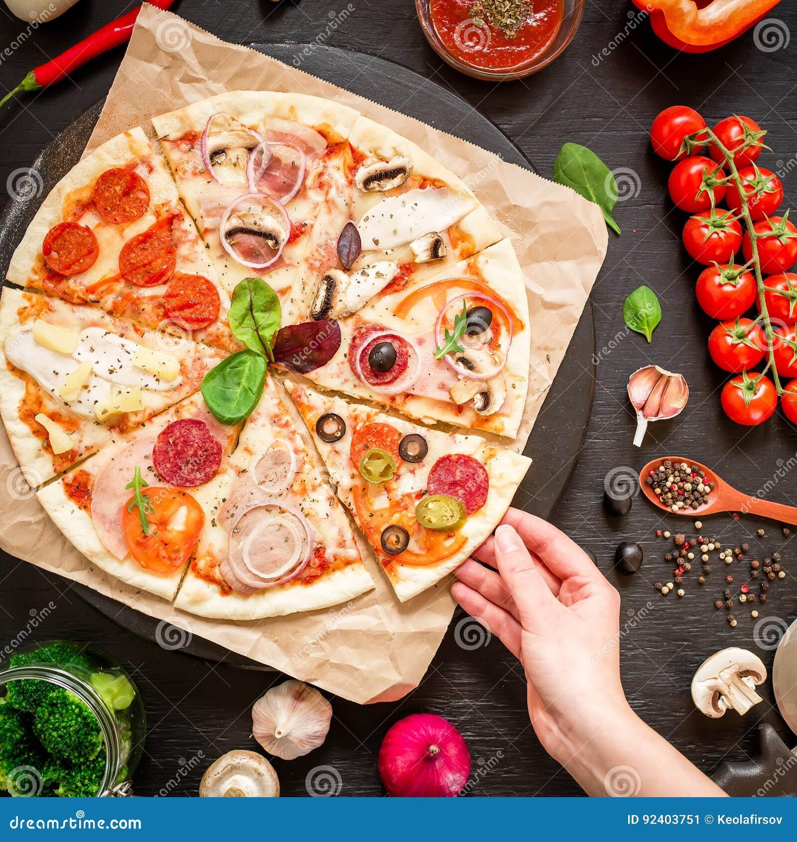 Läcker pizza med ingredienser och kvinnahanden på den mörka tabellen Lekmanna- lägenhet Top beskådar italienska matlagningmatingr