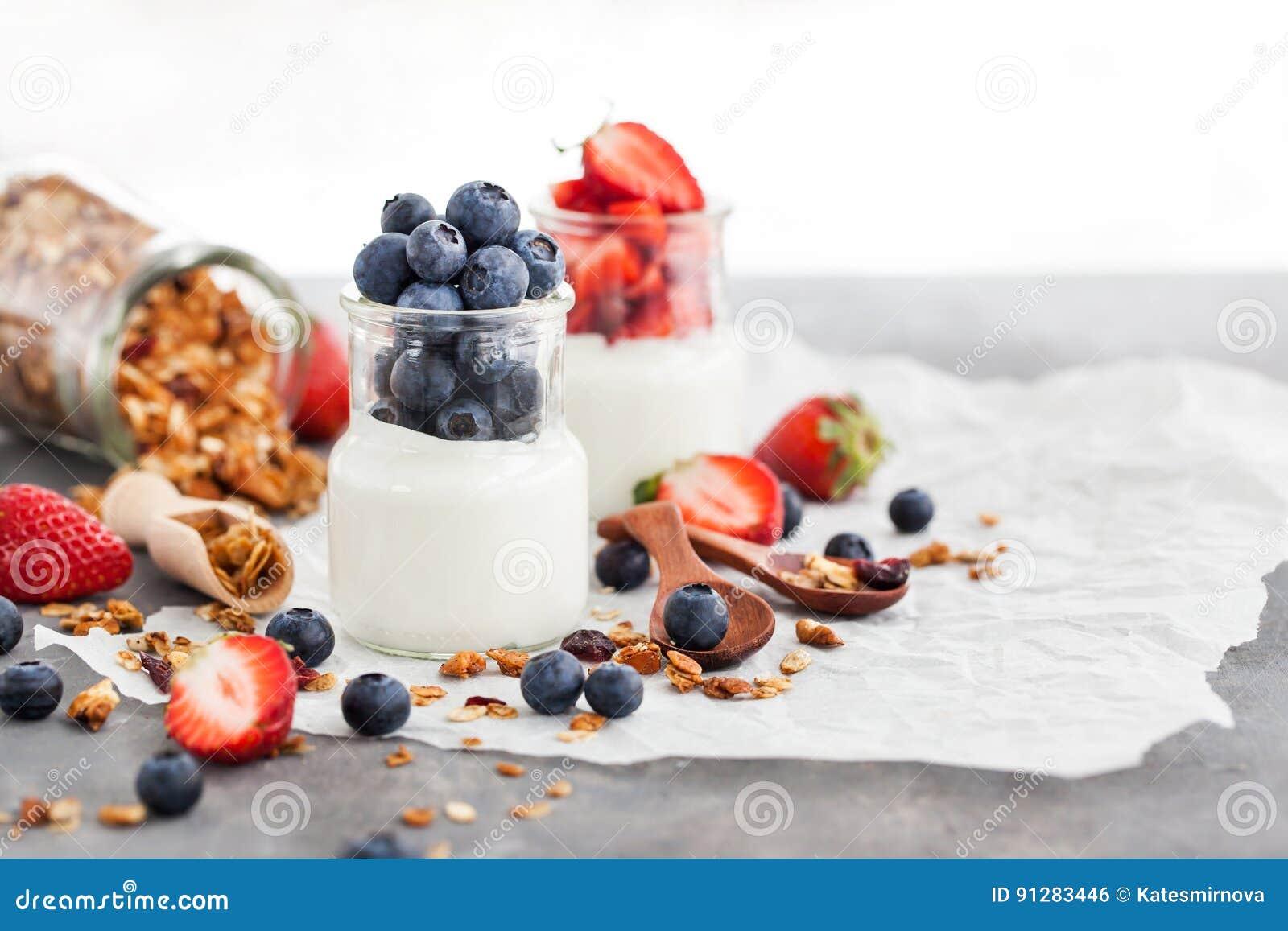 Läcker vanlig yoghurt med det nya blåbäret och jordgubben i a