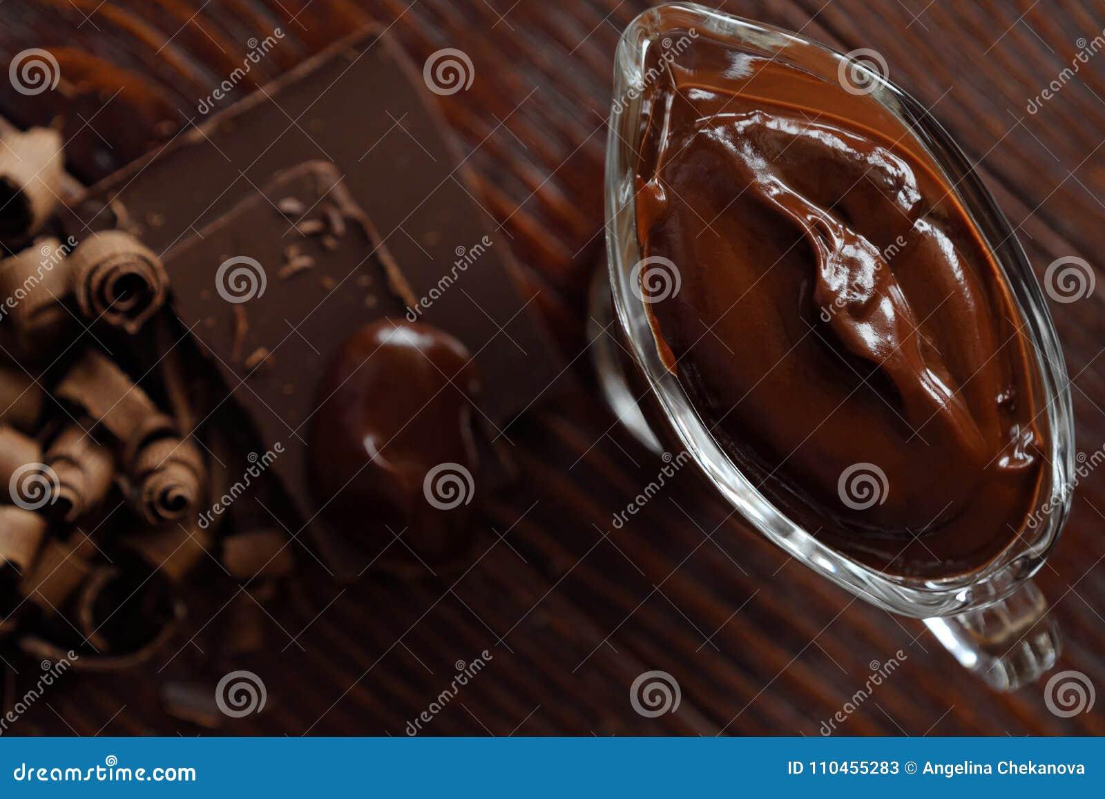 Läcker varm choklad i exponeringsglas på en brun bakgrund