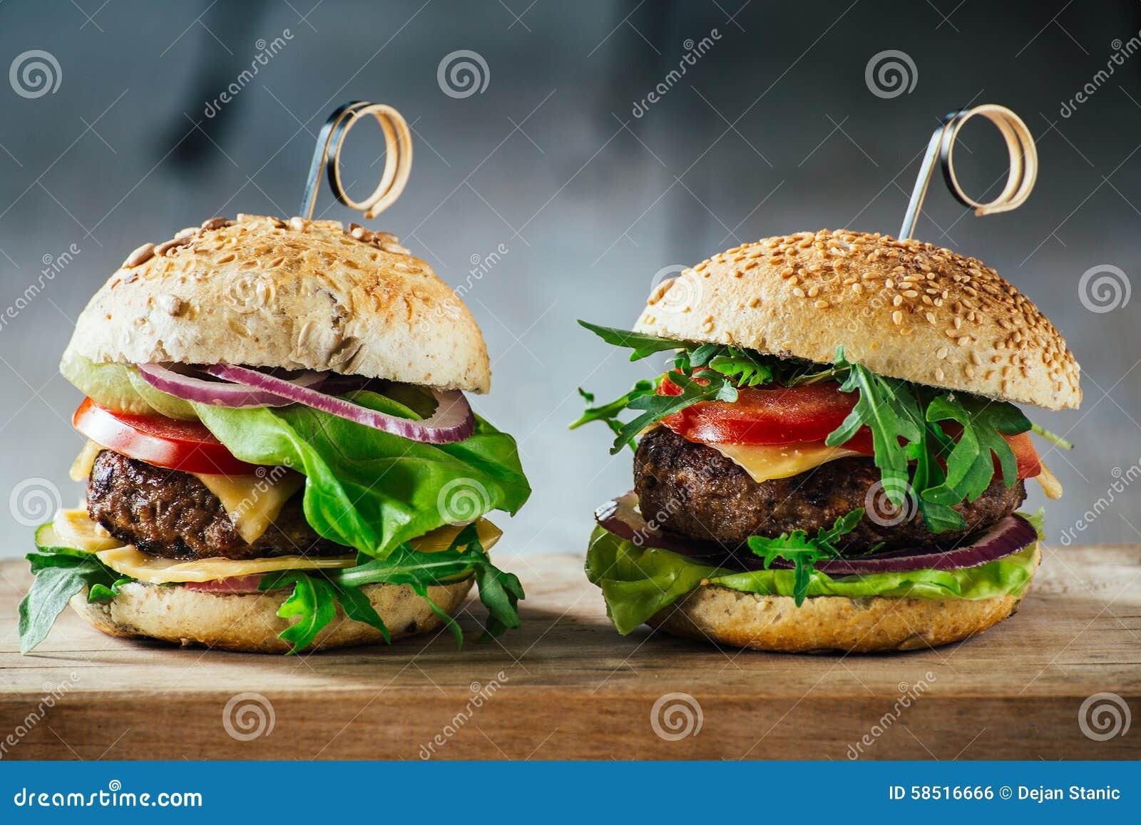 Läckra hamburgare med nötkött, tomaten, ost och grönsallat
